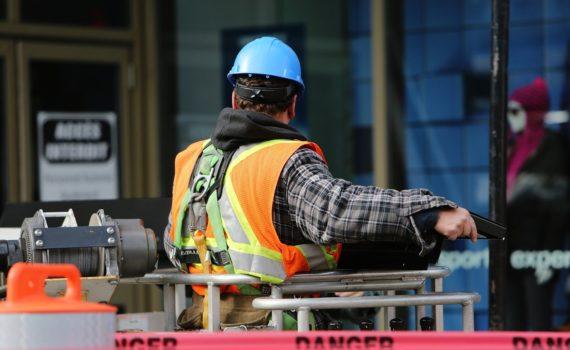 Pracownik budowlany w niebieskim kasku, na wysięgniku